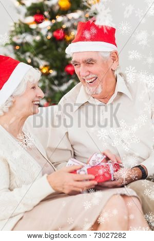 Elderly couple exchanging christmas gifts against snow falling