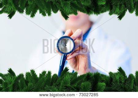 Doctor holding out stethescope with focus on object against fir tree branches forming frame