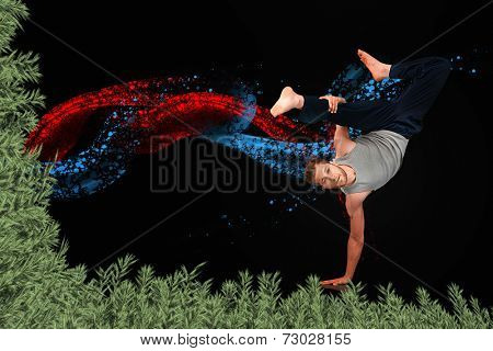 Break dancer showing his agility and balance against green fir branches