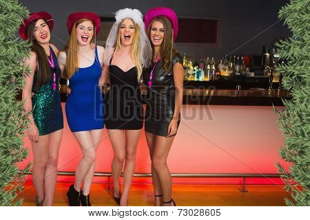Laughing friends having a hen party against green fir branches