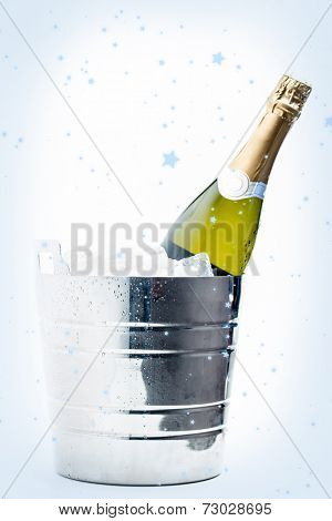 Composite image of snow falling against bottle of champagne chilling in ice bucket
