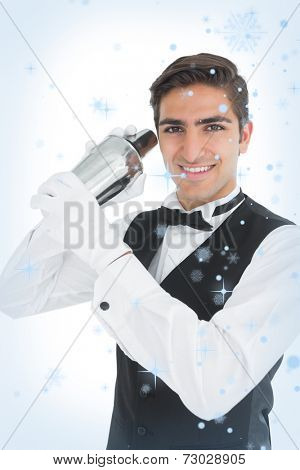 Attractive young barkeeper shaking a drink against snow falling
