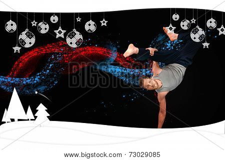 Break dancer showing his agility and balance against christmas themed frame