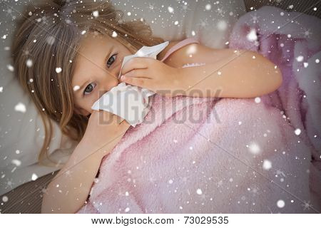 Composite image of girl suffering from cold as she lies in bed against snow falling