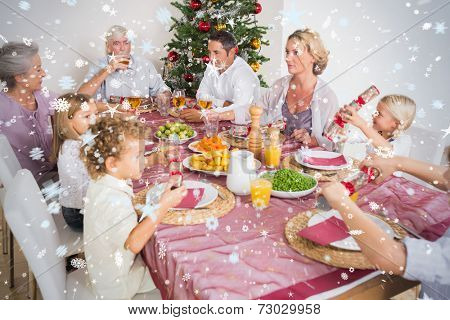 Composite image of Family having christmas dinner against snow
