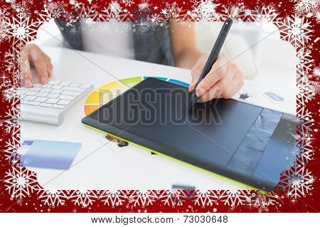 Female photo editor using graphics tablet against snow