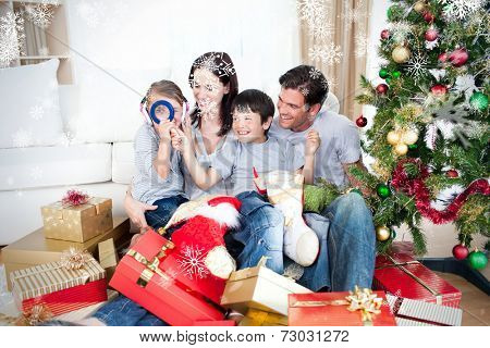 Happy family having fun with Christmas presents against snowflakes