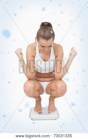 Composite image of Successful young woman crouching on a scales with snow falling