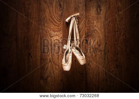 Ballet shoes hanged on a wooden wall with the focus on the shoes