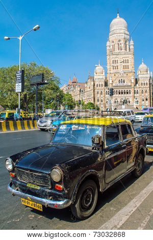 MUMBAI, INDIA - DECEMBER 11: Taxis drive on a street on December 11, 2012 in Mumbai, India. The architecture of Mumbai blends Gothic, Victorian, Art Deco and Indo-Saracenic architectural styles.