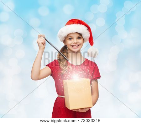 christmas, holidays, happiness and people concept - smiling girl in santa helper hat with gift box and magic wand over blue lights background