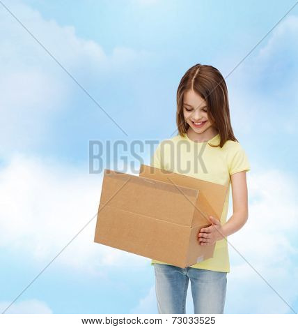 advertising, childhood, delivery, mail and people - smiling little girl holding open cardboard box and looking into it over cloudy background