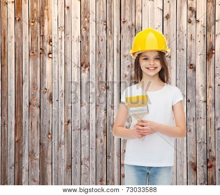 painting, building, childhood and people concept - smiling little girl in protective helmet with paint brush over wooden fence background