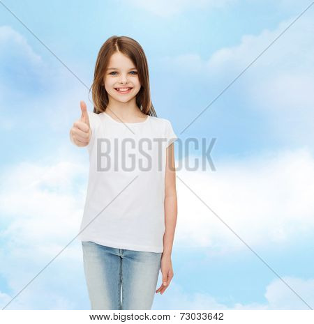advertising, dream, childhood, gesture and people - smiling little girl in white blank t-shirt showing thumbs up over cloudy sky background