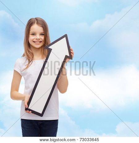 advertising, direction, air, aviation, and childhood concept - smiling little girl with white blank arrow pointing up over cloudy sky background