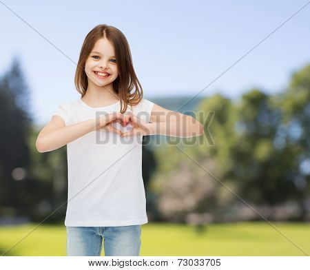 advertising, childhood, nature, charity and people - smiling girl in white t-shirt making heart-shape gesture over green park background