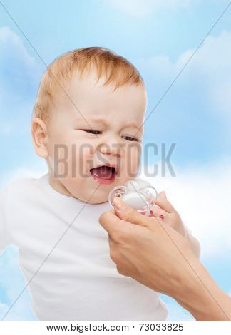 child and toddle concept - crying baby with dummy