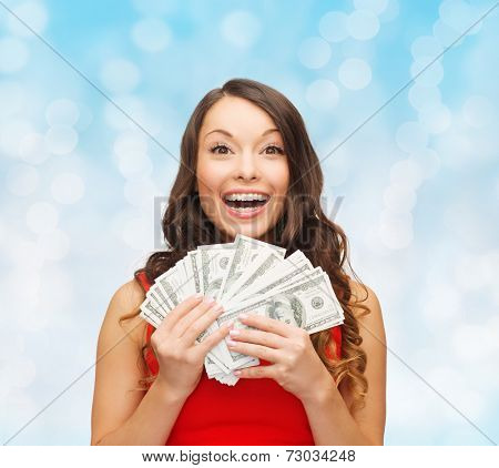 christmas, sale, banking, winning and holidays concept - smiling woman in red dress with us dollar money over blue lights background