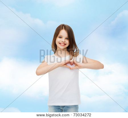 advertising, charity, childhood and people - smiling little girl in white t-shirt t making heart-shape gesture over cloudy sky background