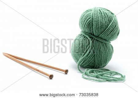 Skein of green yarn with knitting needles