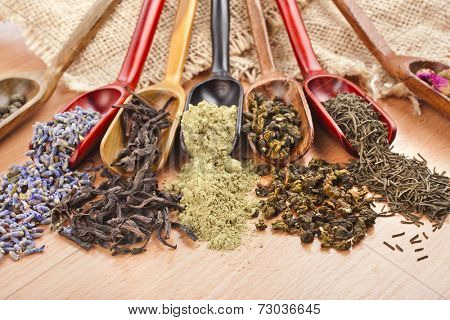 assortment of dry tea in scoops on wooden table background, top view
