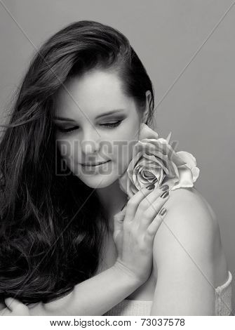 Portrait of a beautiful young brunette woman. Wearing long loose curly hair, posing with a flower. Against grey studio background. Spa concept in black and white