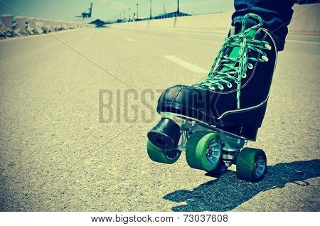 closeup of a young man roller skating on a no traffic road, with a retro effect