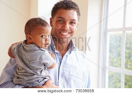Smiling Father Standing By Window With Baby Son At Home