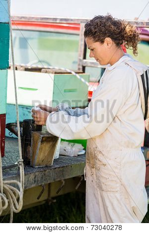 Side view of young female beekeeper fueling smoker for removing honey from hives on truck