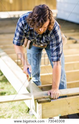 Mid adult manual worker cutting wood with saw at construction site