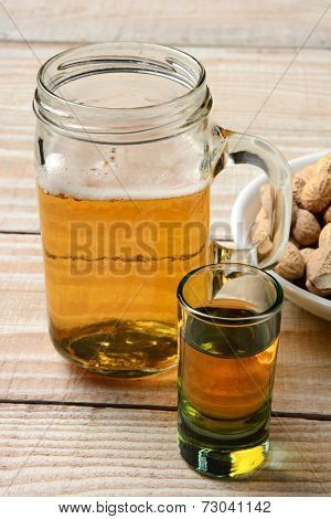 Closeup of a shot of whiskey,a mug of beer and a bowl of peanuts. Vertical format on a rustic wood table.