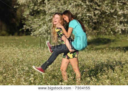 Two Beautiful Young Women Piggy- Backing In Blooming Meadow
