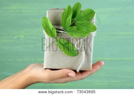 Female hand holding natural style handcrafted gift box with fresh leaves and rustic twine, on wooden background