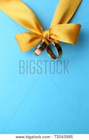 Wedding rings tied with ribbon on color background