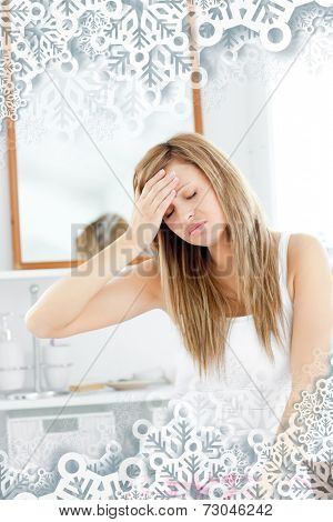 Dejected woman having a headache sitting in the bathroom with snowflakes on silver