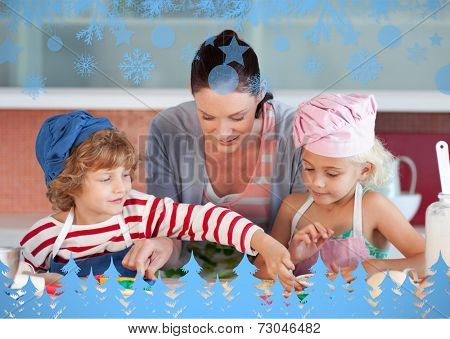 Smiling mother baking with her children against snow flake frame in blue