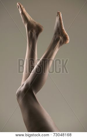Legs and bare feet in air