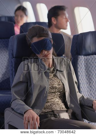 Young woman sleeping on airplane with eye mask