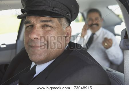 Portrait of chauffeur with businessman in car