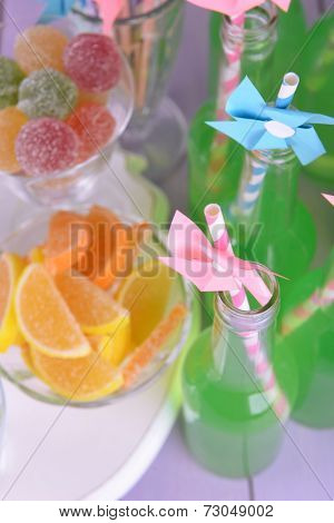 Bottles with drink and sweets on table  close up