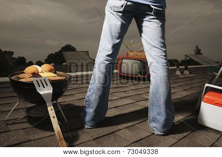 Young man watching television and barbecuing on roof