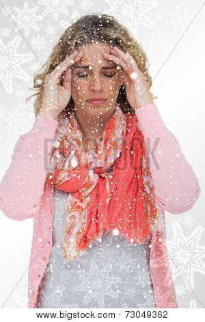 Blonde girl touching her temples because of a headache against snowflakes on silver