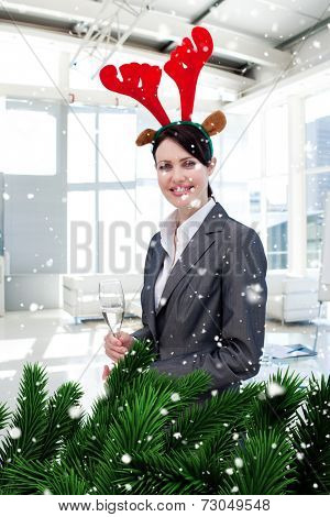 Composite image of a Smiling businesswoman with a novelty Christmas hat drinking Champagne against snow falling