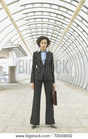 Full length portrait of businesswoman in walkway