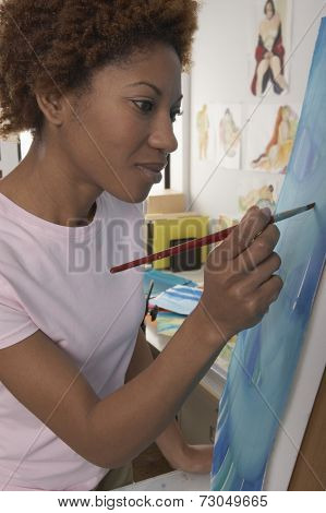 Profile of woman painting on canvas