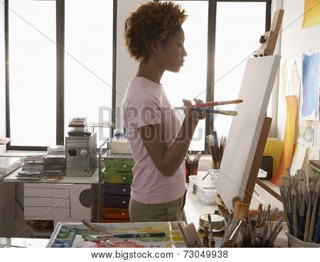 Profile of female artist looking at canvas