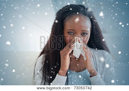Composite image of close up of woman on sofa blowing her nose against snow falling