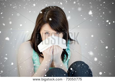 Composite image of portrait of a sick attractive woman blowing against snow falling
