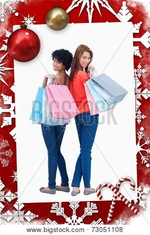 Smiling teenagers looking behind them after shopping against christmas themed page