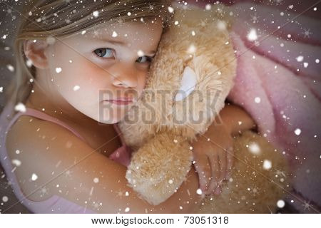 Close up portrait of a girl with stuffed toy against snow falling